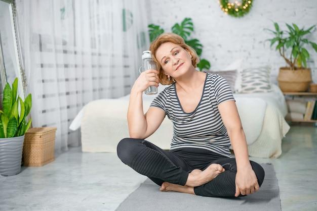 Oude vrouw, het rusten op, oefen mat, na, fitnesstraining, vasthouden, fles water,