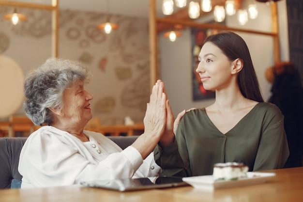 Oude vrouw in een café met jonge kleindochter
