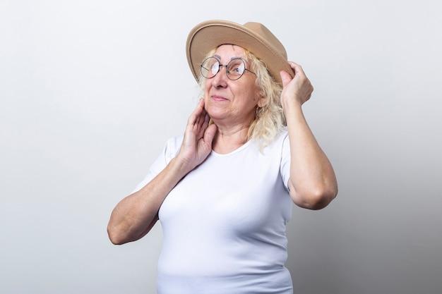 Oude vrouw in een hoed met een bril op een lichte achtergrond.