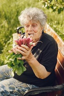 Oude vrouw in een hoed met verse radijs