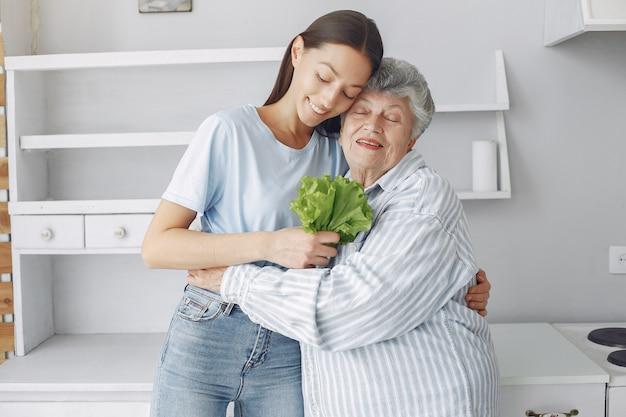 Oude vrouw in een keuken met jonge kleindochter