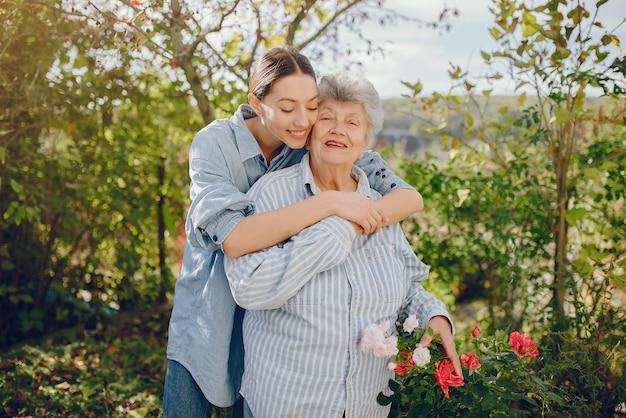 Oude vrouw in een tuin met jonge kleindochter