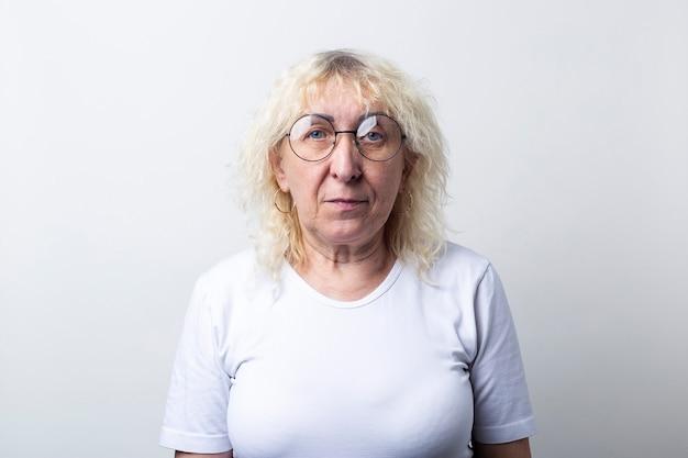 Oude vrouw in een wit t-shirt met een bril op een lichte achtergrond.