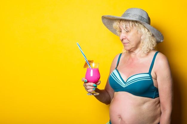 Oude vrouw in een zwembroek met een hoed kijkt naar een cocktail op een gele ondergrond