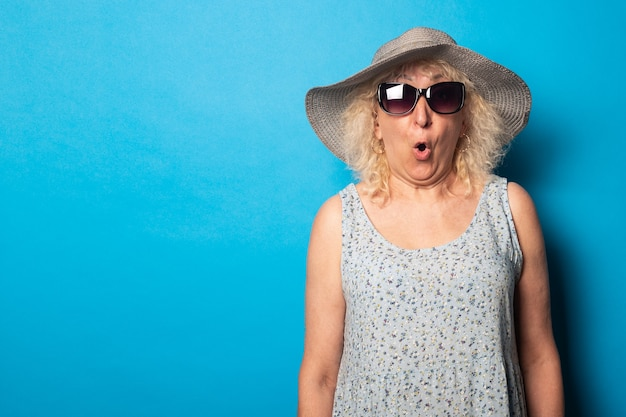 Oude vrouw in jurk en hoed met zonnebril