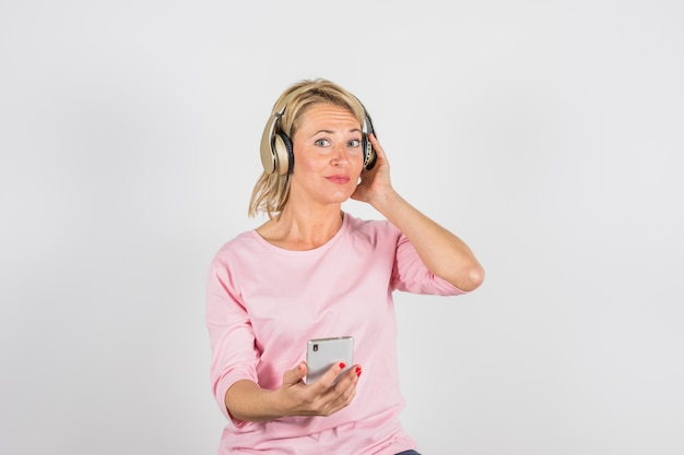 Oude vrouw in roze blouse met hoofdtelefoons die smartphone gebruiken