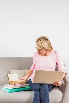 Oude vrouw in roze blouse met laptop en hoop van boeken op bank