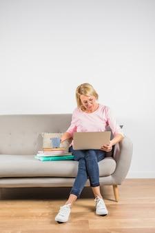 Oude vrouw in roze blouse met laptop en kop op hoop van boeken op bank