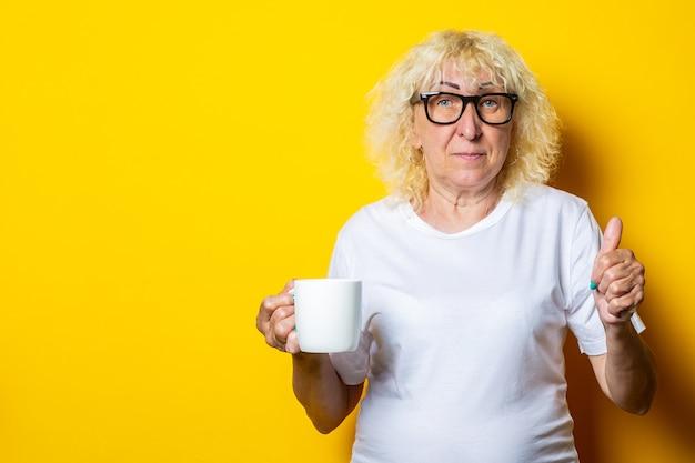 Oude vrouw in wit t-shirt en glazen houdt een kopje thee op een gele muur.