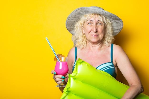 Oude vrouw in zwembroek met cocktail houdt luchtbed op gele ondergrond