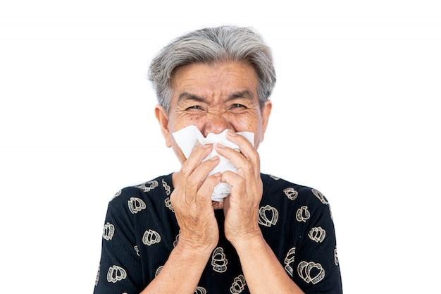 Oude vrouw is verkouden, gebruikt een tissue om haar mond te bedekken bij hoesten en niezen, covid 19