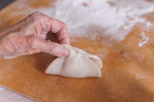 Oude vrouw kookt manti.