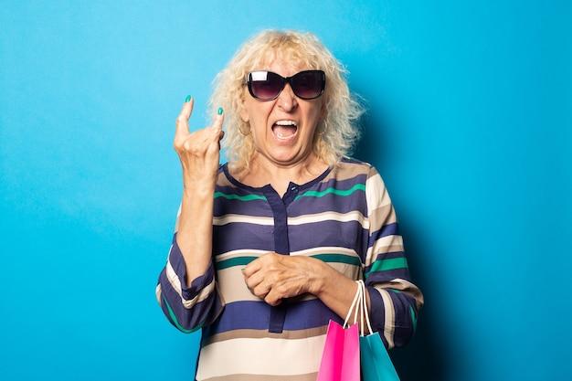Oude vrouw met bril houdt boodschappentassen en toont rock and roll-gebaar op blauwe ondergrond