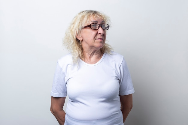 Oude vrouw met bril kijkt naar de zijkant op een lichte achtergrond.