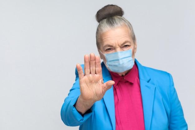 Oude vrouw met chirurgisch medisch masker dat stopbord toont bij camera