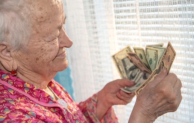 Oude vrouw met dollar contant geld thuis