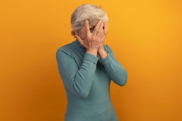 Oude vrouw met een blauwe coltrui die het gezicht bedekt met handen die naar de voorkant kijken door vingers die op een oranje muur zijn geïsoleerd met kopieerruimte