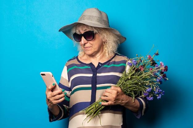 Oude vrouw met een boeket bloemen kijkt naar de telefoon