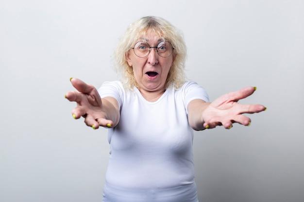 Oude vrouw met een bril strekt haar armen uit om te knuffelen op een lichte achtergrond.