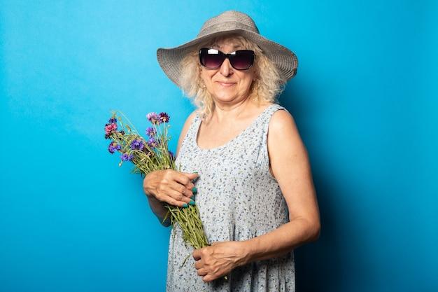 Oude vrouw met een glimlach in een hoed met brede rand en een jurk met een boeket bloemen op een blauwe muur.