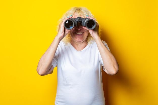 Oude vrouw met een glimlach in een wit t-shirt kijkt door een verrekijker op een gele muur.