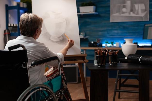 Oude vrouw met een handicap die een tekening van een vaas van tafel maakt