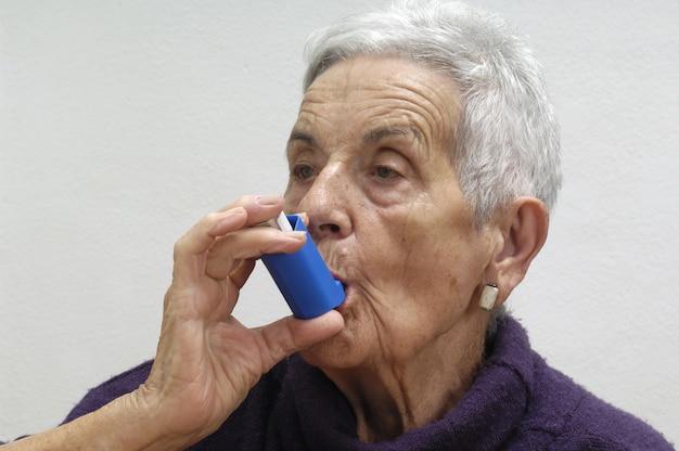 Oude vrouw met een inhalator