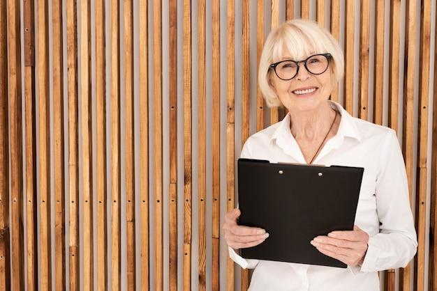 Oude vrouw met een klembord op houten achtergrond