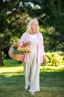 Oude vrouw met een mand die op weide loopt