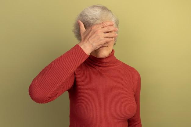 Oude vrouw met een rode coltrui en een zonnebril die de ogen bedekt met de hand geïsoleerd op een olijfgroene muur met kopieerruimte