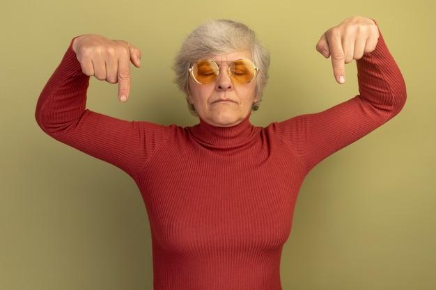 Oude vrouw met een rode coltrui en een zonnebril die naar beneden wijst met gesloten ogen geïsoleerd op een olijfgroene muur