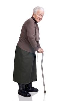 Oude vrouw met een stok poseren in studio op een witte achtergrond