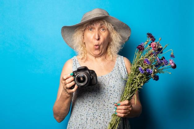 Oude vrouw met een verbaasd gezicht in een hoed met brede rand en een jurk met een boeket bloemen en een camera op een blauw oppervlak