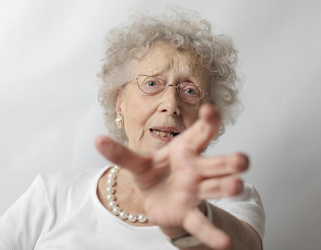 Oude vrouw met grijs haar die weigert een foto te maken