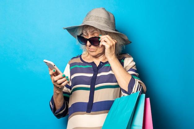 Oude vrouw met hoed en bril houdt boodschappentassen en kijkt naar haar telefoon op een blauw oppervlak