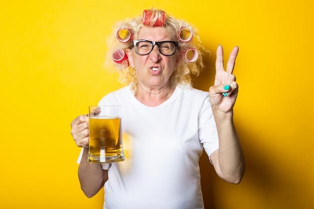 Oude vrouw met krulspelden met een glas bier toont een gebaar van twee vingers, overwinningen en vrede op een geel vlak