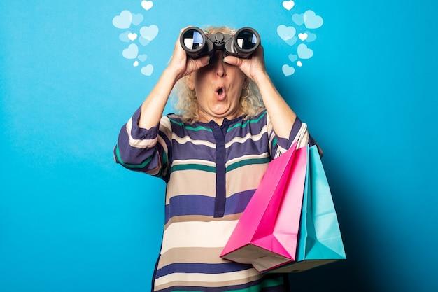 Oude vrouw met verbaasd gezicht boodschappentassen te houden en door een verrekijker op blauwe muur te kijken.