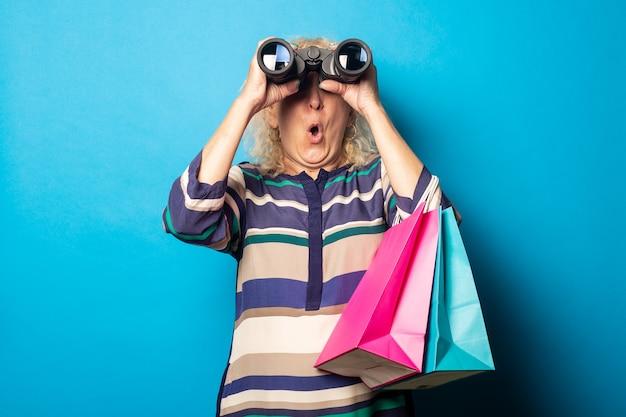 Oude vrouw met verbaasd gezicht boodschappentassen te houden en door een verrekijker op blauwe ondergrond te kijken