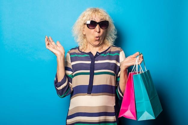 Oude vrouw met verbaasd gezicht met boodschappentassen op blauwe muur.