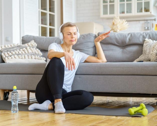 Oude vrouw ontspannen na fitnessactiviteit thuis luisteren naar muziek stressverlichtingsactiviteiten