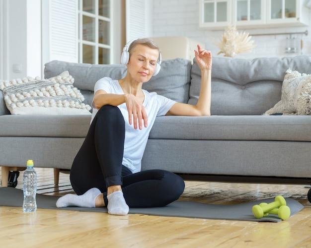 Oude vrouw ontspannen na fitnessactiviteit thuis luisteren naar muziek