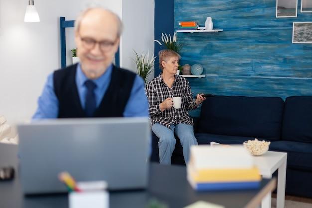 Oude vrouw ontspannen op de bank met een kopje koffie en man is aan het werk