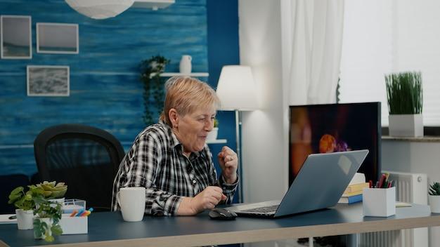 Oude vrouw ontvangt goed nieuws op laptop die thuis werkt