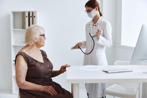 Oude vrouw patiënt bij de dokter stethoscoop