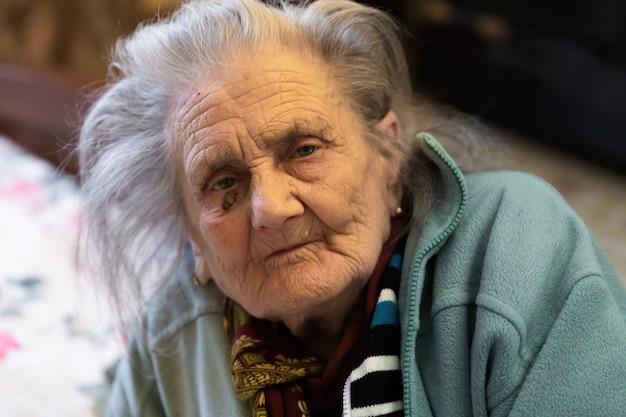 Oude vrouw. portret van zeer oude vermoeide vrouw in depressie binnenshuis zittend op bed