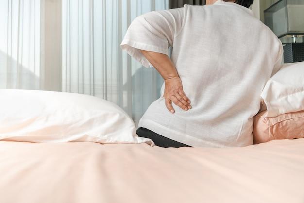 Oude vrouw rugpijn thuis, gezondheidsprobleem concept
