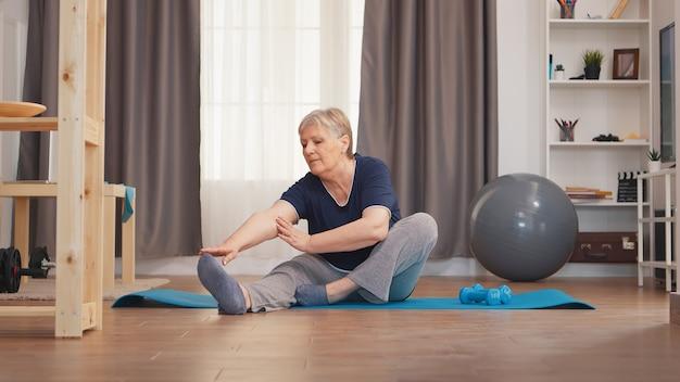Oude vrouw strekkende benen zittend op yoga mat in woonkamer. actieve gezonde levensstijl sportieve oude persoon training workout thuis wellness en indoor training