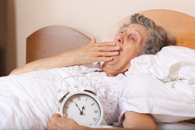 Oude vrouw tussen 70 en 80 jaar gaapt met vintage wekker