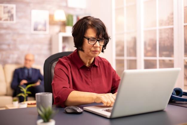 Oude vrouw van in de 60 die laat in de avond een moderne laptop gebruikt in haar gezellige huis