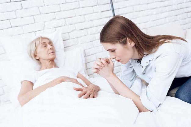 Oude vrouw voelt zich slecht, meisje bidt.